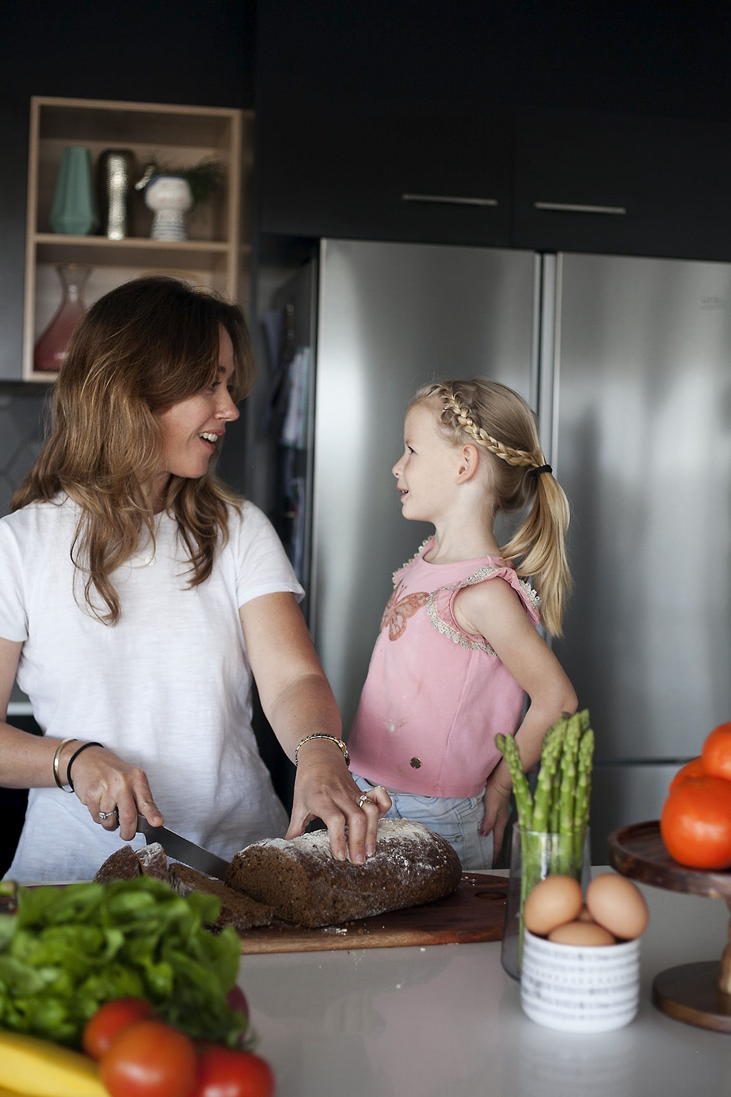 Photo of Erin O'Neill APD non diet dietitian with small child slicing some bread in the kitchen