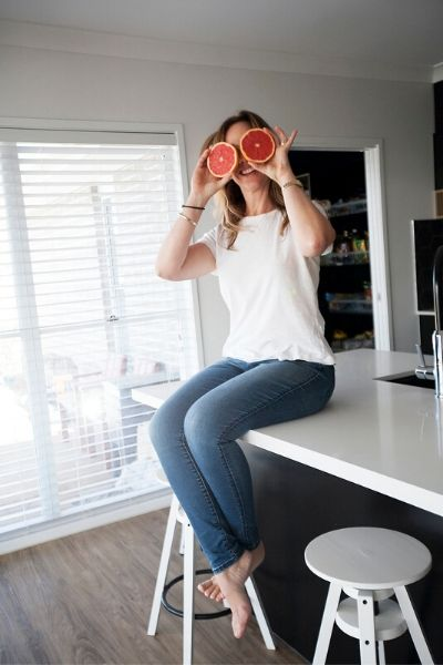 Photo of Erin O'Neil APD online dietitian for busy mums wearing a white t-shirt being silly with grapefruit as eyes