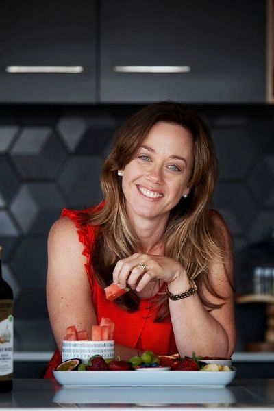 Photo of Erin O'Neill online weight loss coach wearing a bright red top, smiling, and holding a piece of watermelon in her hand.