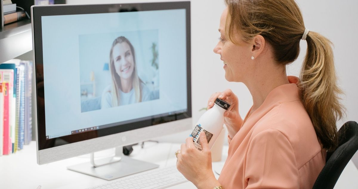 Photo of Erin O'Neill APD sitting at a desk, while chatting on a Zoom call to a female client about her 1:1 weight loss coaching for busy mums